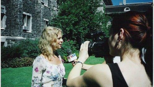 TV station interviewing Agnes Podbielski on set  (character: Caroline)