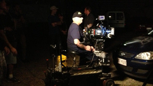 Setting up for an Alexa night car interior travel shoot. Grip rocks my dolly. Lights swing overhead for streetlight. Set of two lights on wheels swing left and right to the rear of the car as following traffic.