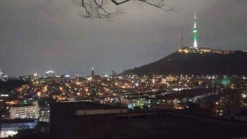 Seoul Tower at night overlooking Itaewon and Yongsan Garrison, Seoul, South Korea.
