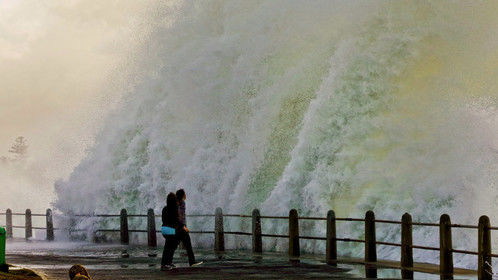 Onlookers watch on as a giant wave crashes on the promenade at Sea Point, Cape Town, South Africa. Picture: Adrian de Kock / 4roomz.com