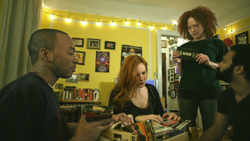 Jennifer (Sarah Schoofs) finds the Meme tape while Kyle (Chaz Cleveland), Carrie (Kitty Ostapowicz), and Tommy (Shivantha Wijesinha) are sifting through their collection of tapes - Promotional still from shooting Meme January 2015