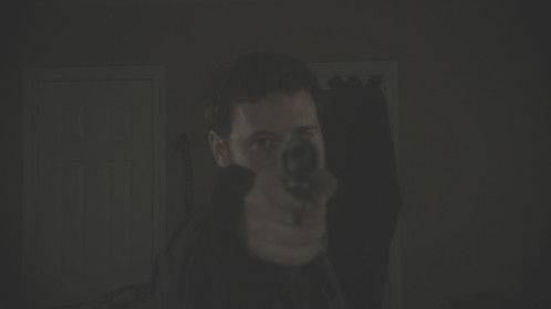Our lead actor points his gun into the camera for a shot.